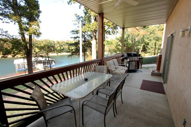 Balcony with table, chairs, and BBQ overlooking lake
