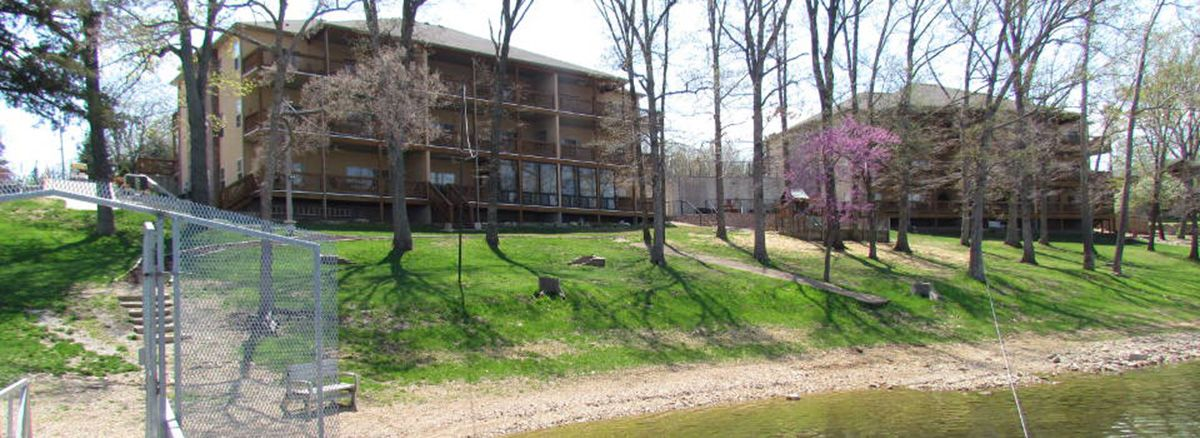 Back of condos with grassy area, trees, and lake