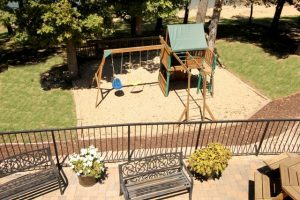 View of small playground from balcony with benches and table
