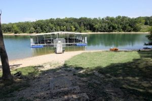 Dock on lake with beach and grassy area